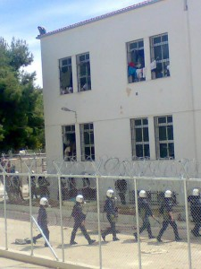 Riot police in the detention centre of Corinth. On the roof a migrant detainee threatening to jump.