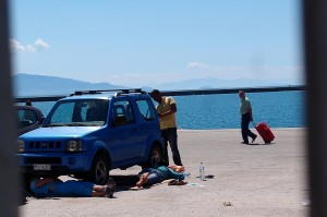 Meanwhile tourists arrive from Aivalik in Turkey and look at the destitute refugees